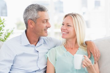 Woman holding coffee cup while looking at man
