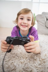 Happy boy playing video game while lying on rug