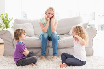 Upset mother looking at children fighting on rug