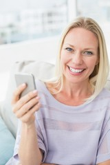 Portrait of smiling woman text messaging through smart phone