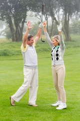 Excited golfing couple cheering