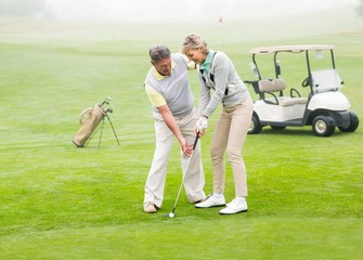 Golfing couple putting ball together