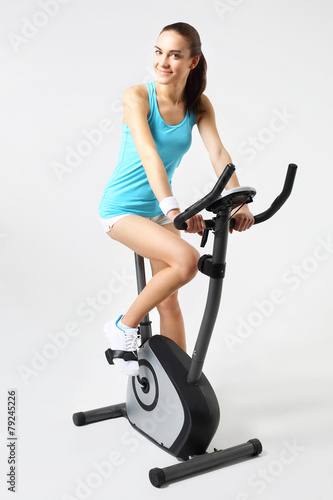 Spinning, kobieta ćwiczy na rowerze stacjonarnym - 79245226