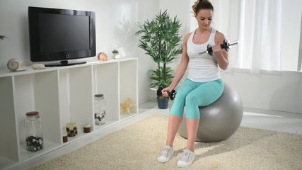 Beautiful young woman doing exercise to strengthen her biceps