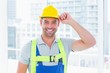 Happy manual worker wearing yellow hard hat - 79247209