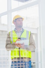 Architect in reflective clothing writing on clipboard at office