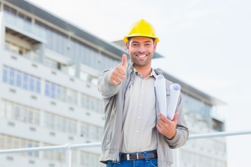 Architect with blueprints gesturing thumbs up outdoors