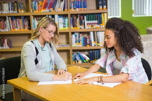Leinwandbild Motiv Student getting help from tutor in library