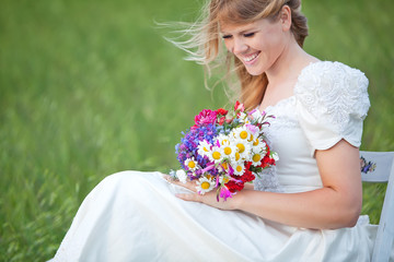 beautiful bride with a flower bouquet on the green grass
