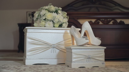 DOLLY MOTION: wedding shoes and bouquet on a white chair