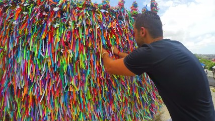 Guy making a wish with the colorful religious brazilian ribbons