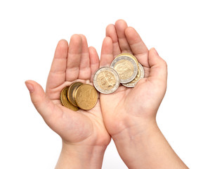 Coins in child's hand on white background
