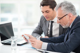 Two businessmen working with tablet computer