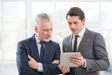 Two businessmen working on tablet computer