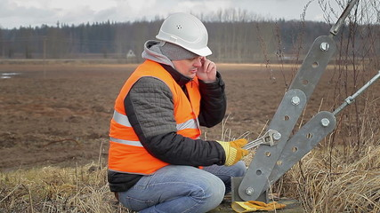 Worker with cell phone andadjustable wrench near tensioner