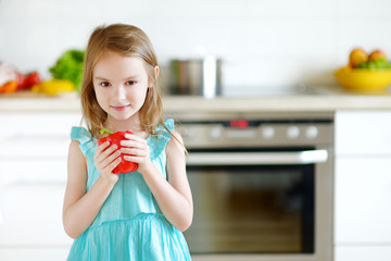 Adorable girl holding vegetables in a kitchen