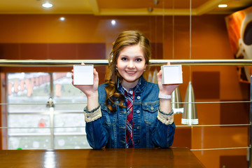 Smiling girl sits and shows the two halves of an empty white box