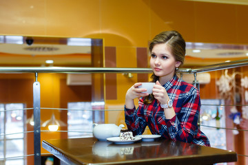 Young nice woman in a plaid shirt drinking tea in a cafe