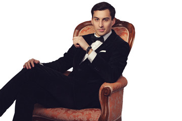 Elegant man in suit sitting on vintage armchair. Luxury.