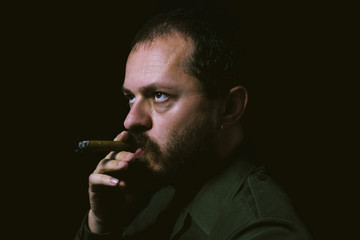 Man with beard and mustaches, smoking the cigar