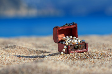 Decorative chest with jewelry  on a beach