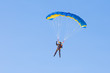 Skydiver on blue and yellow parachute - 79255879