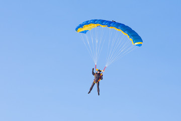 Skydiver on blue and yellow parachute