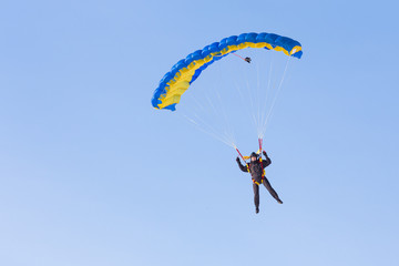 Skydiver on blue and yellow parachute on background blue sky