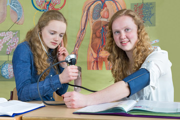 Two teenage girls measuring blood pressure in biology lesson