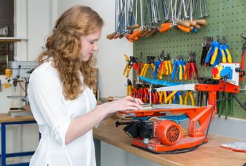 Teenage girl operating electric jigsaw in classroom