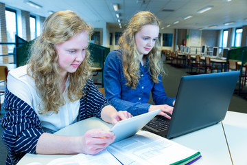 Two girls working on computer and tablet in computer classroom