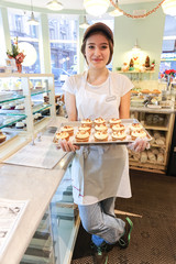 Smiling girl with cupcakes at the bakery counter