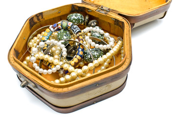 Wooden treasure chest with jewelry on white
