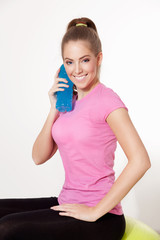 Happy woman with isotonic drink during workout