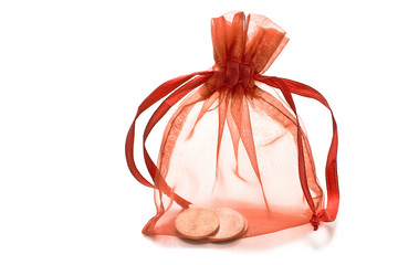 Red gift sack with coins isolated on white