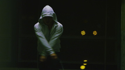 Hooded athlete skipping at night in real time