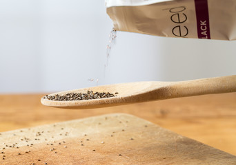 Tiny chia seeds in wooden spoon