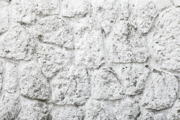 Old white painted wall made of round stones