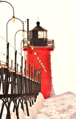 Red lighthouse and pier with snow on neutral background
