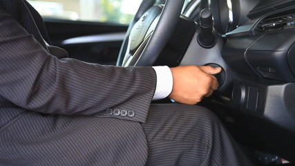 businessman put the key in keyhole to start the car, then drives