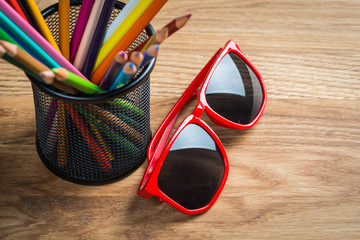 Red sun glasses with bunch of color pencils in a stand