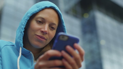 Attractive young woman in a hood using a phone outdoors