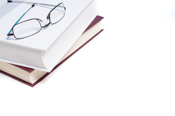 Books and reading glasses on white
