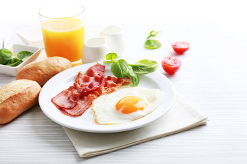 Bacon and eggs on color wooden table and white background