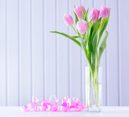 Beautiful pink tulips in vase with decorative hearts