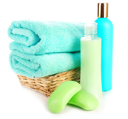 Towels in wicker basket with shampoo bottles and soap isolated