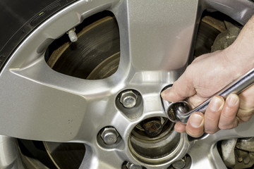 Using a wrench to tighten the nuts on a tire