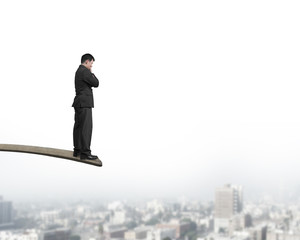 Thinking businessman standing on springboard with cityscape