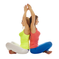 Pretty women practicing yoga in pair