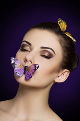 Beautiful woman with bright makeup and butterflies